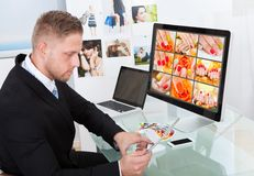 Businessman editing photographs. Businessman sitting at his desk in front of a large screen monitor editing photographs royalty free stock photography