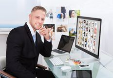 Businessman editing photographs. Businessman sitting at his desk in front of a large screen monitor editing photographs stock images