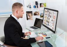 Businessman editing photographs Royalty Free Stock Images