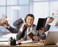 Businessman with eight hands in elegant suit working hold notepa Stock Image