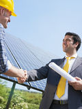 Businessman and electrician shaking hands stock photos