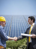 Businessman and electrician shaking hands. Portrait of mid adult italian male engineer holding blueprints and shaking hands to manual worker in solar power stock photo