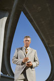 Businessman with electronic organiser beneath overpasses, portrait, low angle view Royalty Free Stock Photography