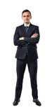 Businessman in an elegant black suit stands with folded arms isolated on a white background. Royalty Free Stock Image