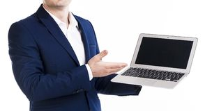 Businessman in elegant blue suit pointing on blank screen of laptop. Empty screen, Isolated on white background, copy space. No fa. Businessman in elegant blue Stock Images
