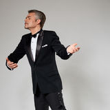 Businessman in elegant suit dancing with an Stock Photo