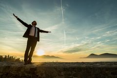 Businessman in elegant suit standing on a wall with his arms spr. Ead widely against a sunrise Royalty Free Stock Photo