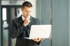 Businessman email laptop. Handsome businessman reading email on his laptop Royalty Free Stock Images
