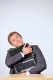 Businessman embracing laptop, looking up Stock Photos
