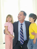 Businessman embracing son and daughter (4-8), smiling Stock Photography