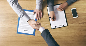 Businessman employed after a job interview. Employer hiring and giving an handshake to the candidate after the job interview, hands close up top view Stock Photography