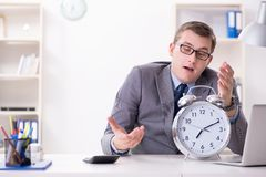 Businessman employee in urgency and deadline concept with alarm. Clock Stock Photo