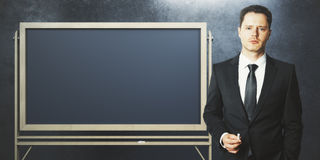 Businessman with empty blackboard. Handsome european businessman with empty blackboard on concrete wall background. Education and information concept. Mock up Royalty Free Stock Images