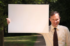 Businessman with empty board. Businessman holding empty board in a city park Stock Photography