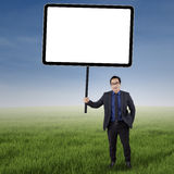 Businessman with empty copyspace at field. Portrait of male worker in business suit, standing on the meadow while holding an empty board Stock Images