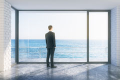 Businessman in empty loft room with big window in floor and ocea. N view, close up Stock Images