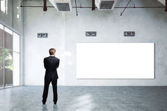 Businessman in an empty room with an empty white board Royalty Free Stock Images