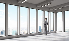 Businessman in empty room looking at big city. Man in empty office room looking at big city through large window. Concept of thoughtfullness. 3D render Stock Photography