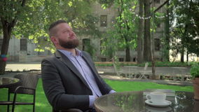 Businessman ends reading book during coffe break. Outdoor. Steadicam shot. He is young and has beard. He is dressed on shirt and jacket. At backgroung there is stock video