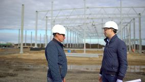 Businessman engineer architect contractor customer manager builder in hard hats having agreement handshake on. Construction site. Two businessmen engineers stock video footage