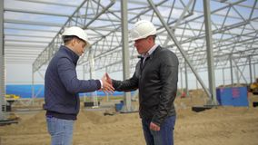 Businessman engineer architect contractor customer manager builder in hard hats having agreement handshake on. Construction site. Two businessmen engineers stock footage