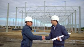 Businessman, engineer, architect, contractor, customer, manager, builder in hard hats having agreement handshake on. Construction site. Two businessmen stock footage