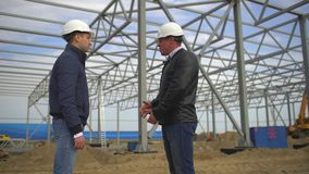 Businessman, engineer, architect, contractor, customer, manager, builder in hard hats having agreement handshake on. Construction site. Two businessmen stock video footage