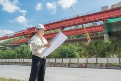 Businessman or Engineer or Architect wearing Hardhat and safety. Vest supervise Motorway or Highway Project Development holding Blueprint beside Infrastructure stock photos