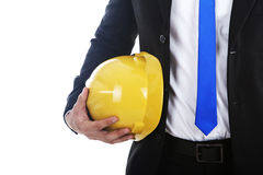Businessman with engineer helmet. A businessman holding an engineer helmet isolated on white Royalty Free Stock Image