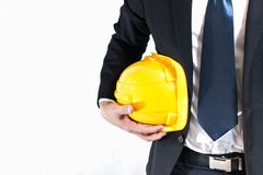 Businessman or engineer holding yellow helmet. For workers security. A helmet under his arm against on white background Stock Photo