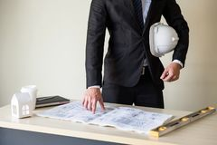 Businessman engineer  manager check project plan. Engineering businessman manager with white helmet and black suit pointing forefinger to engineer project plan Stock Photo