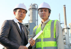 Businessman and engineer oil refinery. Businessman and engineer standing in front of an large oil refinery Royalty Free Stock Photography