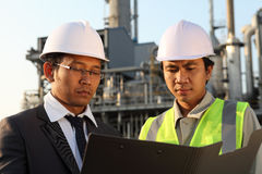 Businessman and engineer oil refinery. Discussing a new project with large oil refinery background Stock Photos