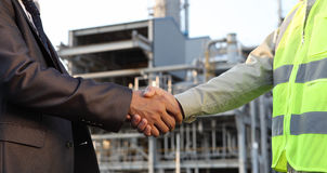 Businessman and engineer oil refinery. Businessman and engineer handshake closing a deal in front of an large oil refinery Royalty Free Stock Photo
