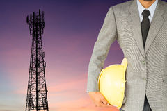 Businessman engineer and telecommunication tower at sunset Stock Image