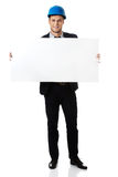Businessman enginner holding empty banner. Royalty Free Stock Images