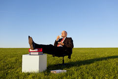 Businessman Enjoying Coffee On Chair In Grassy Field Against Sky Royalty Free Stock Images