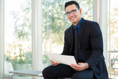 Businessman enjoying his work. Attractive young businessman wearing glasses and reviewing some documents at work Stock Photos