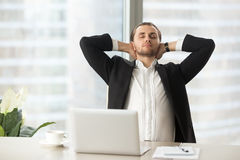 Businessman enjoys break after good work done. Tired businessman sitting at work desk with laptop, resting with hands behind head. Office worker relaxing at Stock Photography