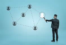 Businessman enlarging one of the social network icons connected by dotted lines with a magnifier Stock Image