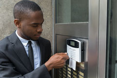 Businessman Entering Code In Security System. Young African Businessman Entering Code In Security System royalty free stock photography