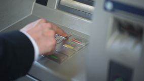 Businessman entering his pin code on keyboard of ATM, banking services, finance. Stock footage stock video