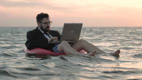Businessman enthusiastically working at a laptop swaying on the waves of a reservoir and sitting on a children`s