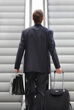 Businessman on escalator with bag and trolley. Business travel Stock Image
