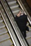 Businessman on Escalator with Cellphone Stock Photo