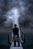 Businessman at escalator under clouds Stock Image