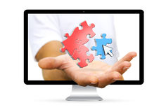 Businessman escaping from computer with puzzle icons in his hand. Businessman going out of a computer screen with puzzle icons flying over his hand Royalty Free Stock Photography