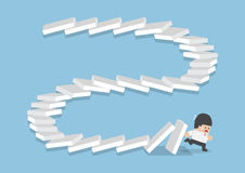 Businessman escaping from falling dominos. Domino effect, bankruptcy, business crisis concept Stock Photography