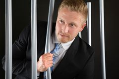 Businessman Escaping From Prison. Portrait Of Young Adult Businessman Escaping From Prison Royalty Free Stock Photo