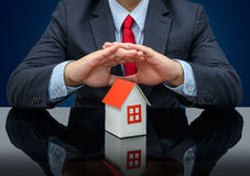 Businessman or estate agent and holding a model house Stock Images